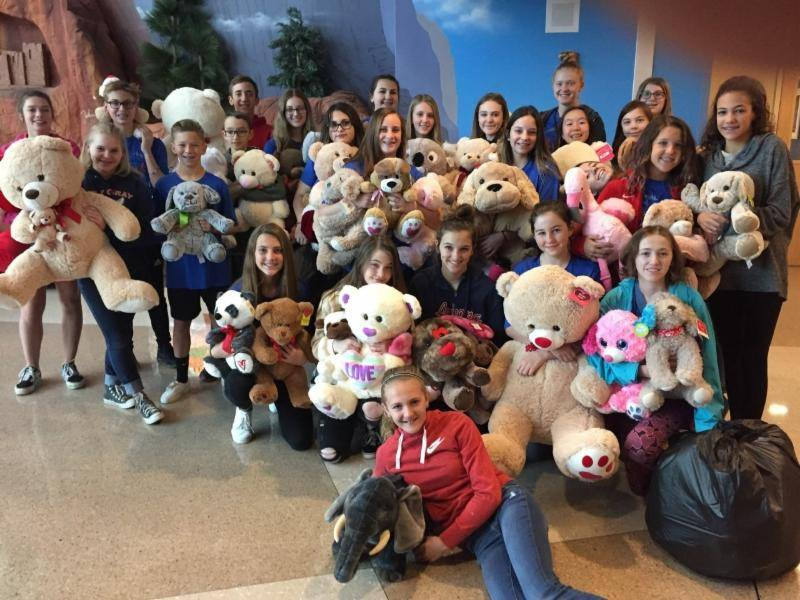 junior high students holding teddy bears