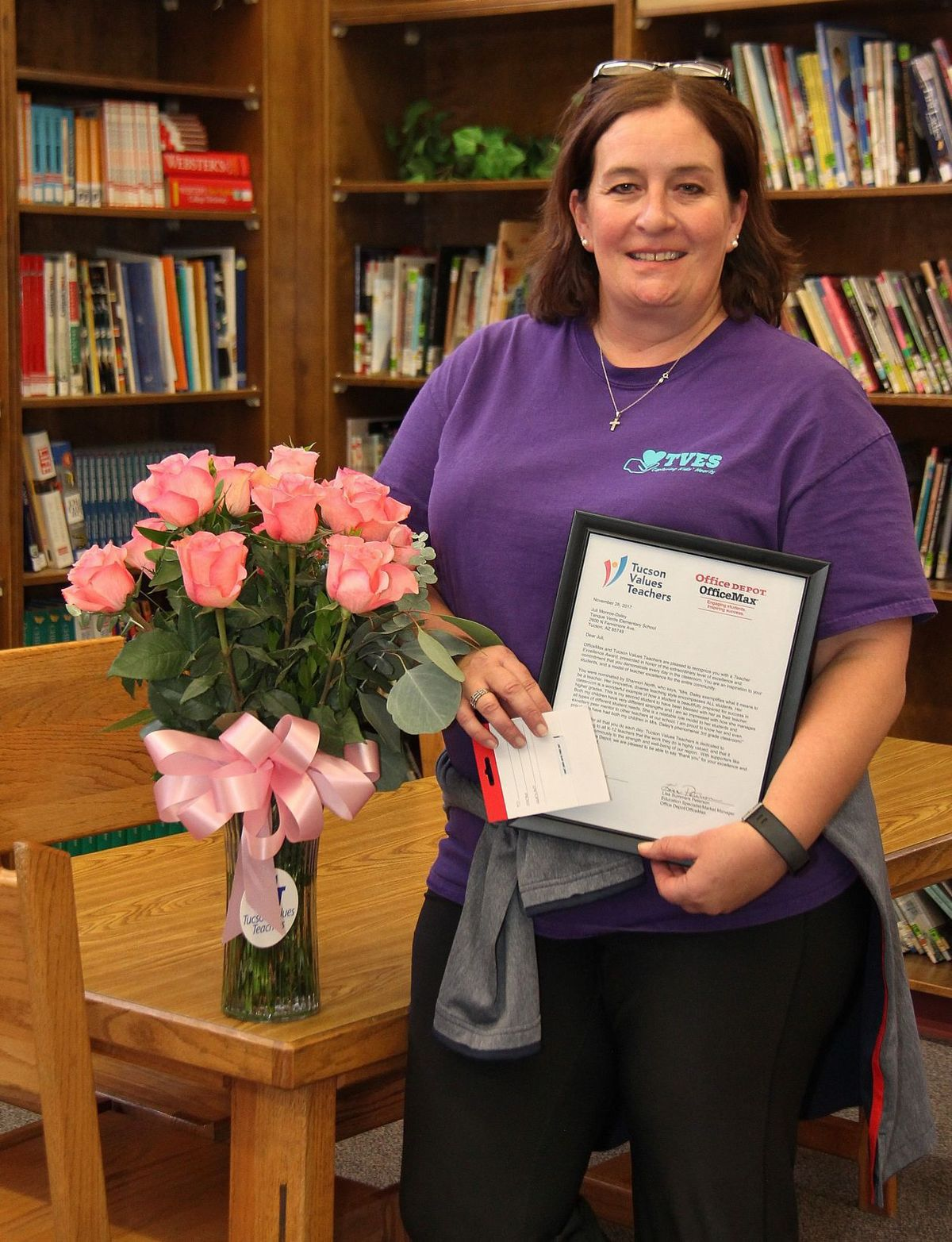 teacher with award and flowers